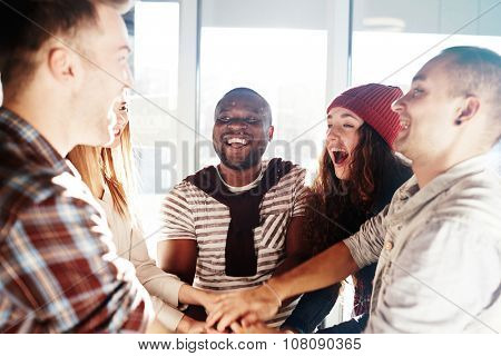 Group of ecstatic friends making pile of hands