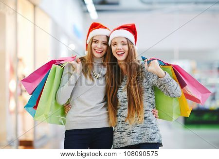 Female shoppers with paperbags looking at camera