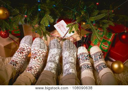 Feet of man, woman, and child in socks by Christmas tree
