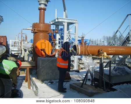 Russia, Yuzhno-Sakhalinsk - November 18, 2014: Preparatory work for the pipeline welding. Construction of an oil and gas pipeline. Industrial equipment.