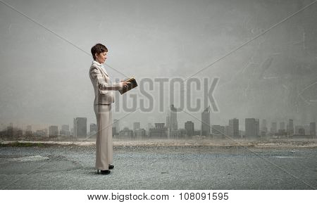 Adult woman in suit with old book in hand