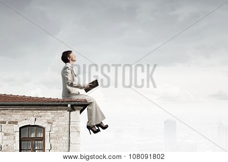 Adult woman in suit with old book in hand sitting on roof
