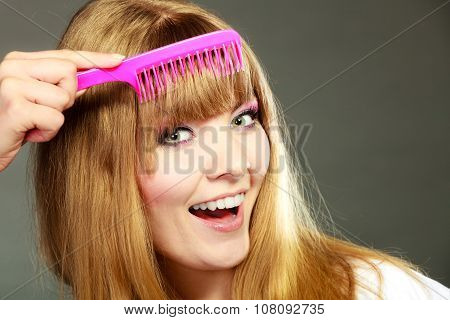 Closeup Woman Combing Her Fringe With Pink Comb