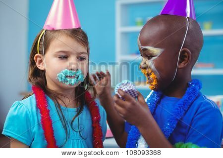 Smiling kids with icing on their faces at the birthday party