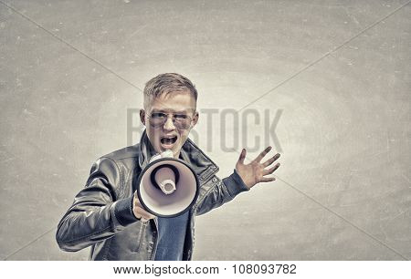 Young man in casual screaming emotionally in megaphone