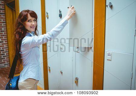 Mature student opening her locker at the university