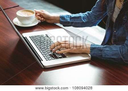 Student using laptop in cafe at the university
