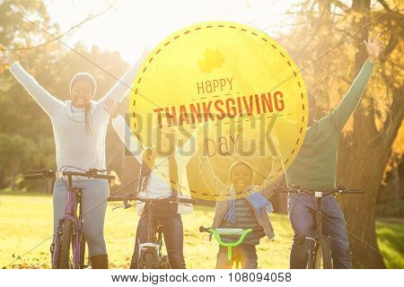 Happy thanksgiving against young smiling family doing a bike ride with arms raised