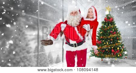 Santa and Mrs Claus smiling at camera against home with christmas tree
