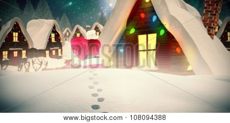 Rear view of santa holding a sack against aurora shimmering in night sky