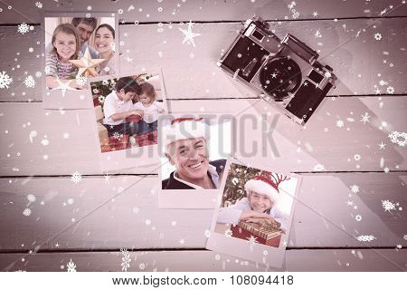 Family Christmas portrait against instant photos on wooden floor