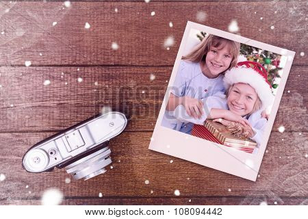 Smiling siblings holding Christmas gifts against view of an old camera