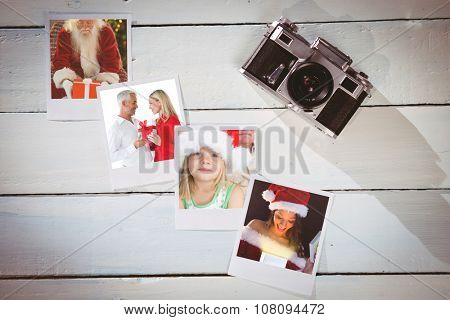 Smiling couple embracing and holding gift against instant photos on wooden floor