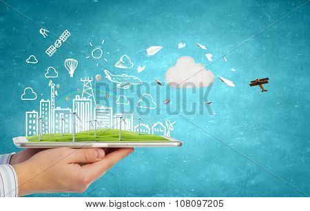 Hands holding tablet with eco concept and windmill generators
