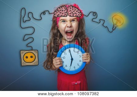 Teenage girl holding a clock and cries of rage charging cord plu
