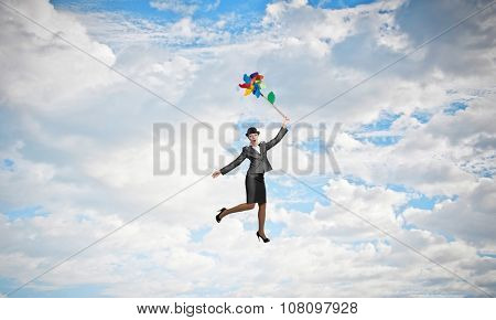 Young businesswoman in suit and bowler hat flying on windmill