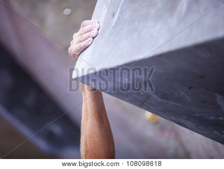 Closeup of man's hand on handhold on artificial climbing wall.