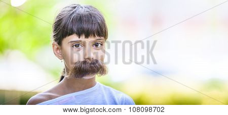 Young girl with fake mustaches hiding her smile.