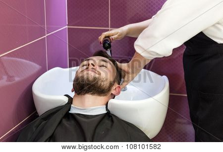 Young man having his hair washed in a hairdressing salon