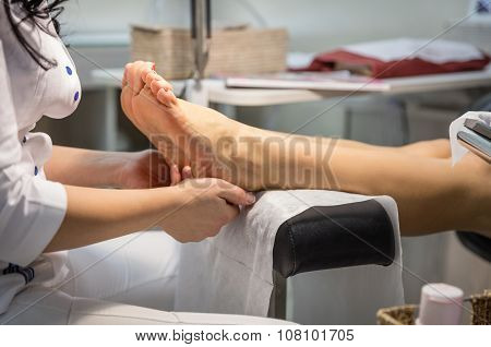 Cropped view of woman getting a pedicure and foot massage