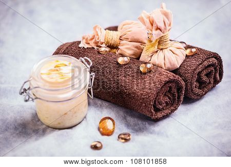 Spa treatment composition: container with body cream, towels, and decorative elements