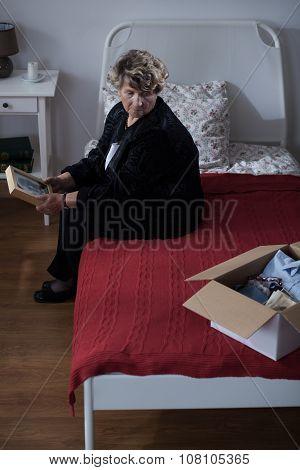 Sad Widow Sitting On Bed