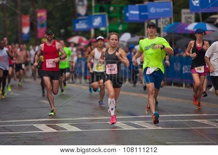 Exhausted Runners Cross Finish Line At Atlanta Peachtree Road Race