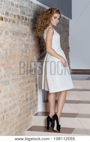 elegant beautiful sexy girl with beautiful hairstyle and bright evening make-up in the evening white