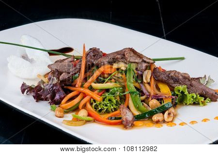 Chopped meat with vegetables served on a white plate