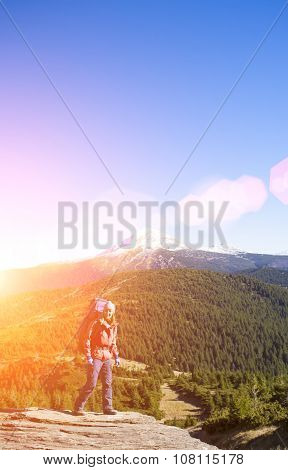 Girl With A Backpack Standing On A Rock.