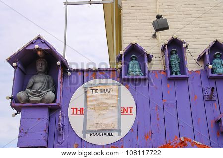 Statues Of Buddha And Chinese Sages Decorating Wooden Wall In Zandvoort, The Netherlands