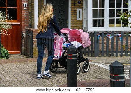Young Woman With Twins Pram Walking Along A Street In Zandvoort, The Netherlands
