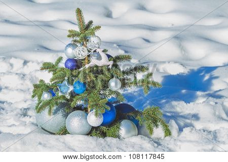 Natural spruce snowy tree decorated with Christmas bright ornaments and baubles
