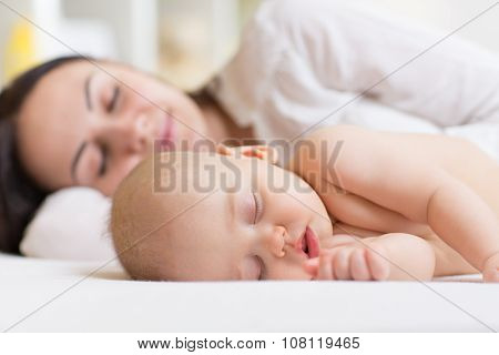 Woman and baby boy relaxing in a white bedroom.