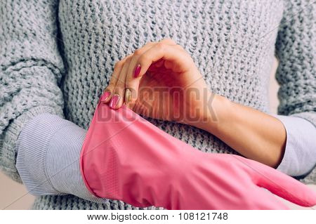 Woman In A Grey Sweater And Bright Pink Manicure Wears Rubber Gloves For House Cleaning