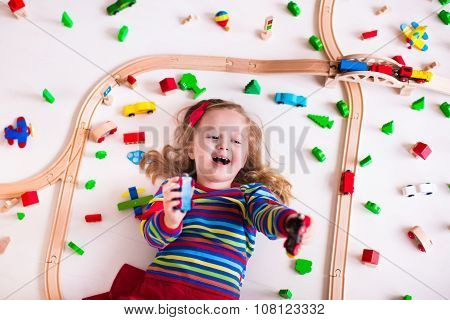 Little Girl Playing With Wooden Trains