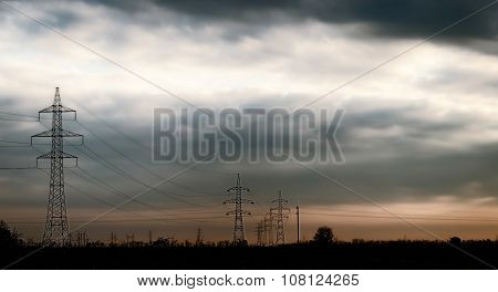 dramatic sky at sunset and silhouette of electric pillars