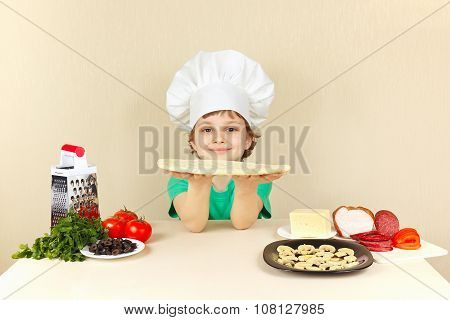 Young smiling chef at the table with ingredients is going to cook pizza