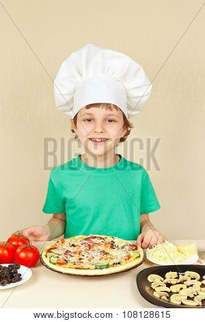 Little boy in hat cook with cooked homemade pizza