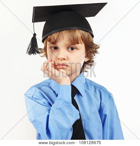 Little pensive boy in academic hat on white background