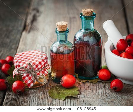 Jar Of Honey, Tincture Bottles And Mortar Of Hawthorn Berries On Wooden Board. Herbal Medicine.