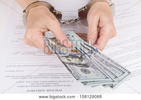 Female Hands In Handcuffs Hold Dollars
