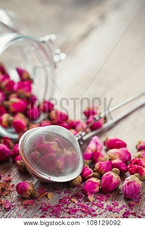 Rose Buds Tea, Tea Strainer And Glass Jar On Rustic Wooden Table. Retro Styled.
