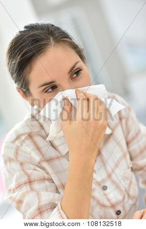 Young woman with cold blowing her nose