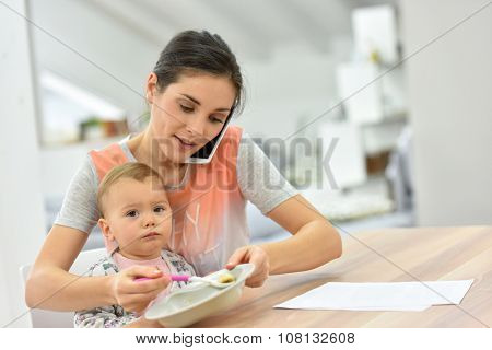 Busy mother on the phone feeding baby a the same time