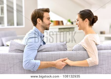 Man and woman in sofa, facing each other and holding hands