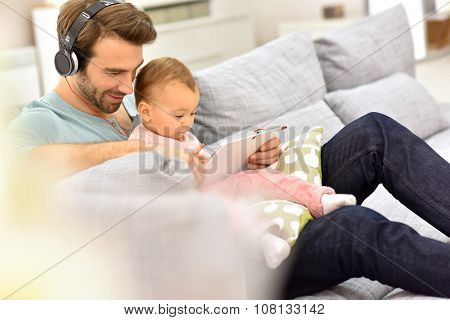Daddy and baby girl in sofa using tablet and headphones