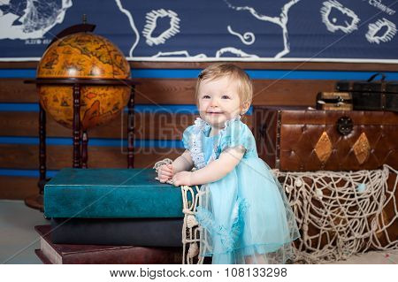 Little princess in a blue dress standing next to a big book