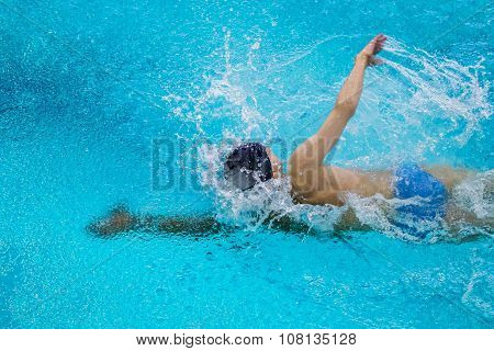 young male athlete swimming freestyle in pool