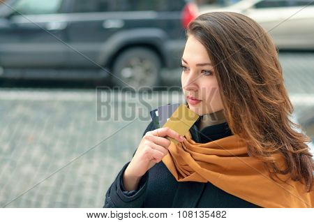 Woman Stands On A City Street With A Credit Card